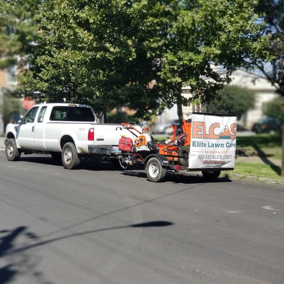A ELCS work truck with an attached trailer. The trailer bears ELCs' logo and name.