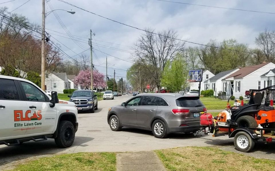 A ELCS work truck bearing their logo and a trailer hauling a large commercial lawn mower parked on the curb of a clients home.