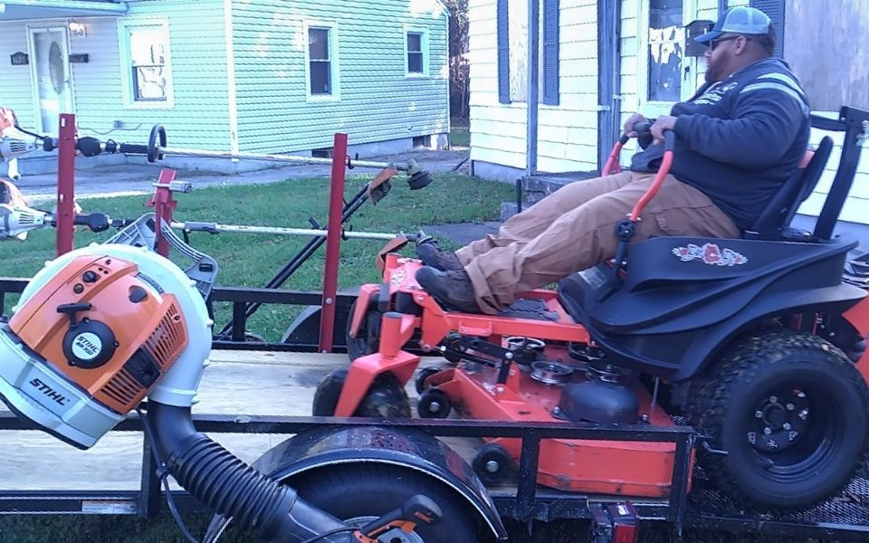 A ELCS employee unloading a large commercial lawn mower from a trailer.