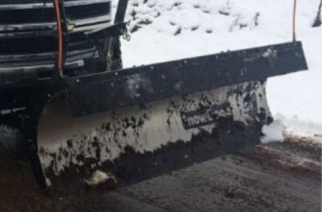 A snow plow being used to clear a road.